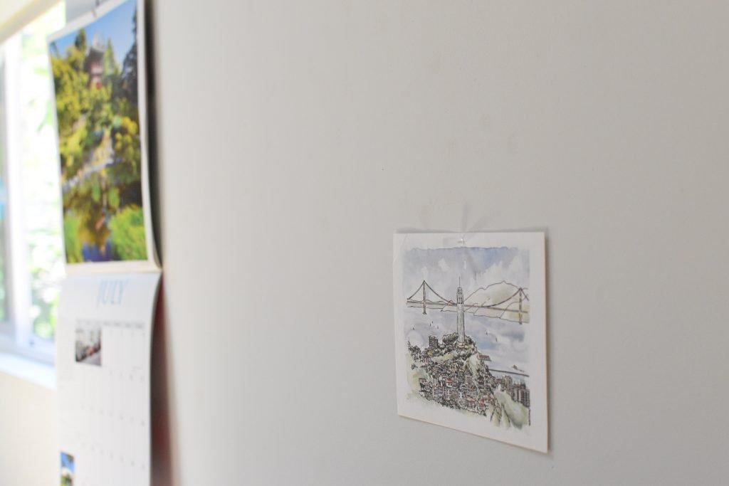 無印良品の針が細い画鋲で壁に留められているポストカード